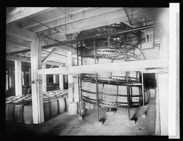 Spiral gravity boiler conveyor for handling barrels and boxes
