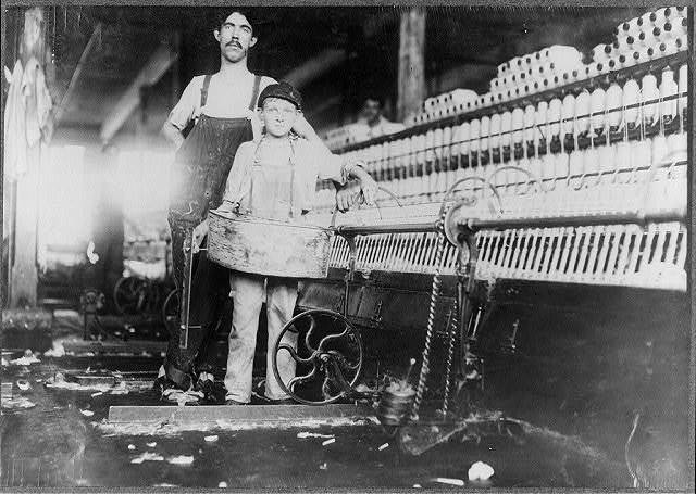 """Street Bretzau, who is a """"Tube-boy"""" in the mule-room of Richmond Spinning Mill, East Lake. Mule spinning is apparently more dangerous than ring spinning. (See bandaged finger.) Photo during working hours.  Location: Chattanooga, Tennessee."""