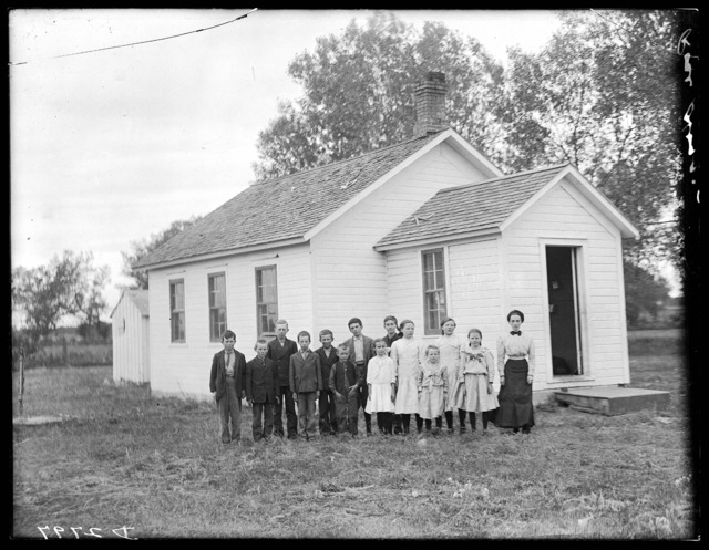 Students and teacher, Miss Rose Hog, in front of  a school house between Gibbon and Shelton, Nebraska in Buffalo County.