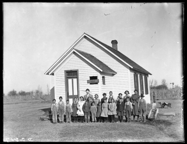 Students and their teacher in front of a country schoolhouse southwest of Elm Creek, Nebraska.