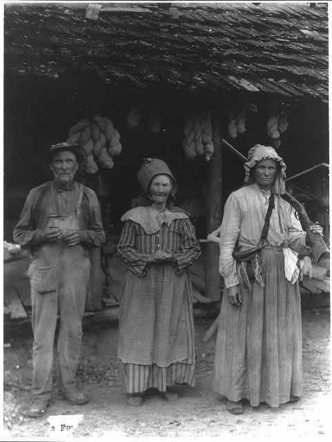 The Faust family, Anderson County, E. Tenn. [Mountain man and 2 women in front of house]