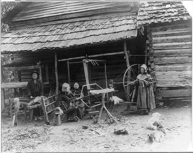 The Faust family, Anderson County, Tenn. at spinning wheel in front of cabin
