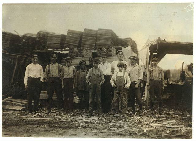 These were the youngest white boys (there were several younger negroes) that I could find working in the Parker Heading Co. Lumber Yards, Poplar Bluff, Mo. (Sometimes called the Great Western Lumber Co.) I went through the buildings and yards. Smallest white boy is Frank Childers, Front St., Poplar Bluff. He and the other small boys help trim and carry strips to make barrel headings.  Location: Poplar Bluff, Missouri.