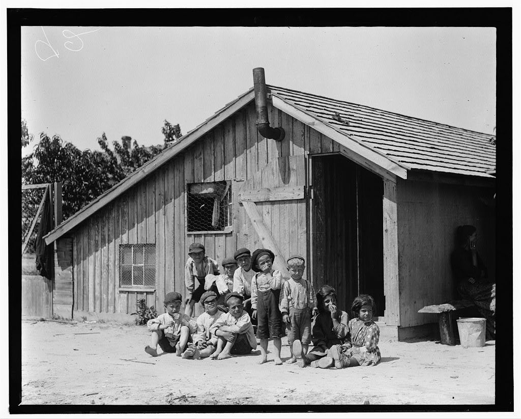 This photo shows what was formerly a chicken coop, in which during the berry season the Arnao family live on Hitchen's farm, Seaford, Del. 17 children and 5 elders live in this made over chicken coop. The age of 10 of the children is given below: 1 Child is 3 years old; 1 Child is 4 years old; 1 Child is 5 years old; 1 Child is 6 years old; 2 Children are 7 years old; 1 Child is 9 years old; 1 Child is 10 years old; 1 Child is 11 years old; 1 Child is 13 years old. Another photo in this collection shows the Arnao family on Truitt's Farm. On the day of the investigation no berries being picked on Hitchen's Farm. The family went over to the Truitt's farm to pick. [Handwritten notation:] See them picking strawberries (Sept 28, 1910) in photos & labels 1128-1129-1130. Edward F. Brown, Investigator.  Location: Seaford, Delaware / Photo by [Lewis W. Hine].