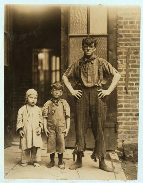 """This picture shows the """"Four Novelty Grahams"""" acrobatic performers at the Victoria Theatre, Philadelphia. The father is 23 years of age. Willie Graham is 5 years of age, and Herbert Graham is 3 years of age. At 9 P.M. on June 10th, 1910, these children were performing on the stage. Four times daily they do a turn which lasts from 12 to 14 minutes. Herbert Graham, the youngest, was said by the father to have commenced performing on the stage as a[n] acrobat when he was 10  months of age. Willie, now 5, is said to be the youngest acrobat in the world. The attached letter head shows some of the stunts these youngsters are engaged in. The mother of these boys was formerly a school teacher, and is now performing with this trio on the stage. The children are bright and strong, but have a playfulness about them which shows them to have forgotten the best years of childhood. Edward F. Brown, Investigator.  Location: Philadelphia, Pennsylvania / Photo by Lewis W. Hine."""