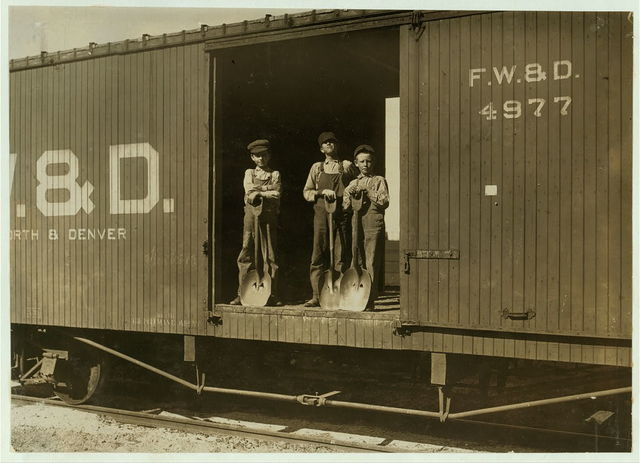 Three Boys Shoveling Zinc Ore from Car Into Wagon, Near Big Bonanza Mine, Aurora, Mo. Youngest boy is Robert Nichols, next larger is Hobart Crawford. They both go to school and work on Saturdays. The other boy works every day.  Location: Aurora, Missouri.