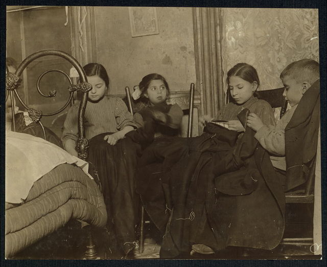 [Three girls and a boy working on garments].  Location: [New York?, New York (State)?]