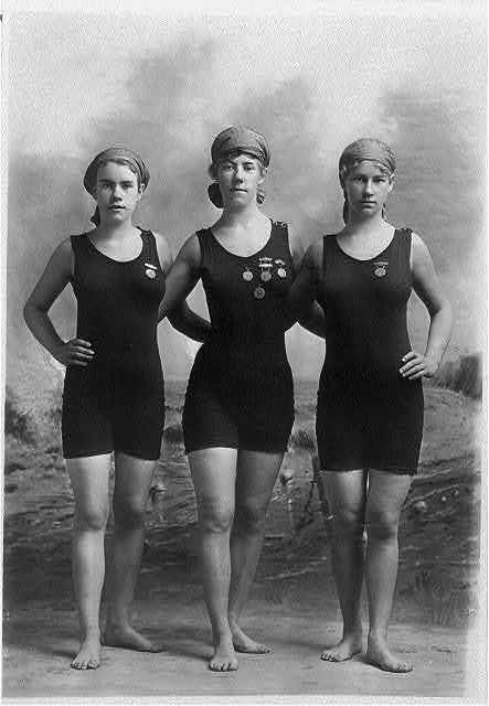 [Three young women posing in swimsuits and wearing their swimming competition medals]