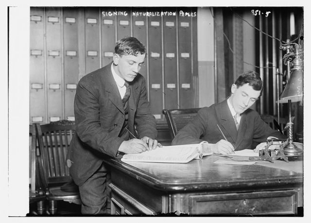 Two new citizens sign naturalizaton papers in judge's chambers, from the Bain Coll. / Bain Collection