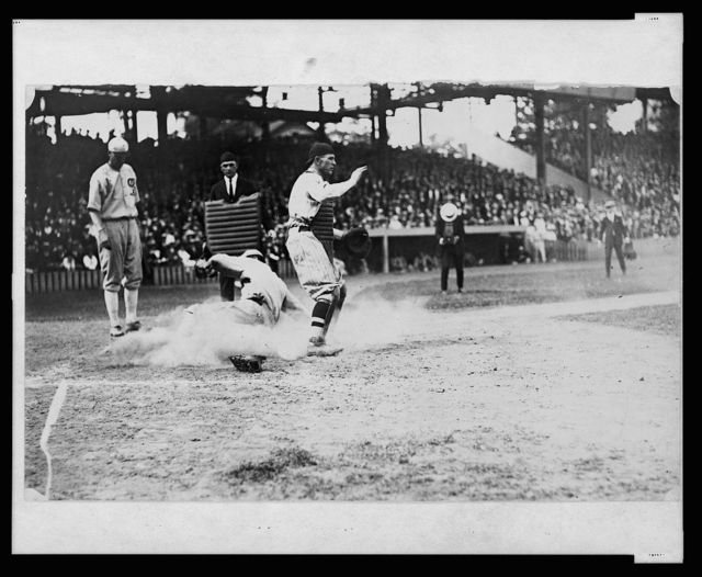[Umpire watches as base runner slides into home plate ahead of the tag during baseball game]