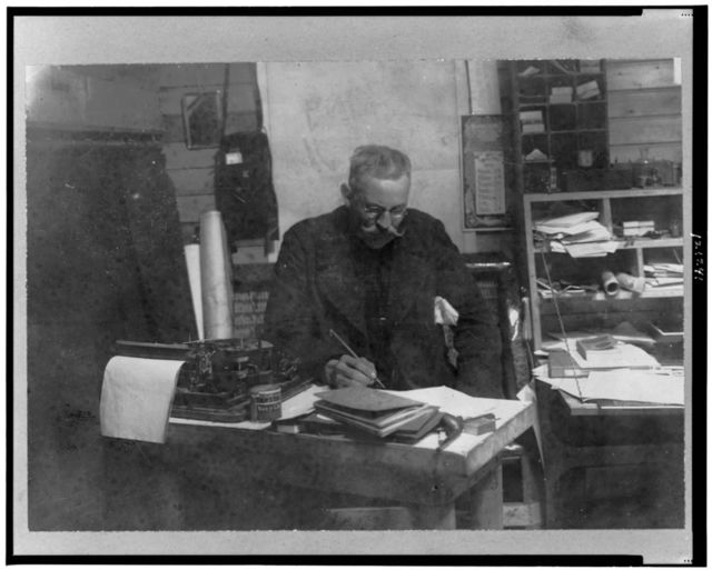 [Walter Wellman, half-length portrait, seated at desk, facing slightly right, with pen in hand, looking downward, Spitzbergen]