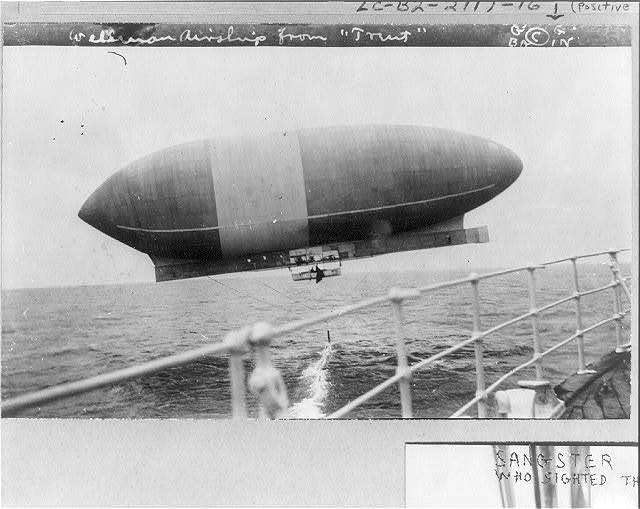"[Wellman airship ""America"" viewed from the RMS TRENT, shown dragging anchor in water]"
