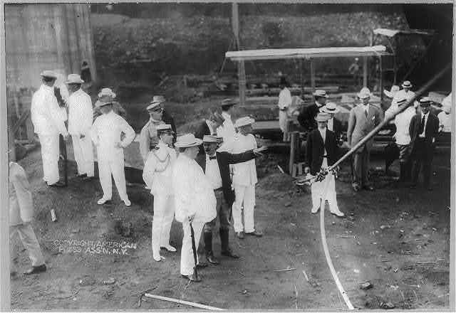 [William Howard Taft, Pres. U.S., full length portrait, standing, right profile, talking to Supt. Williams at Pedro Miguel [Panama]; construction site; other men in background.]