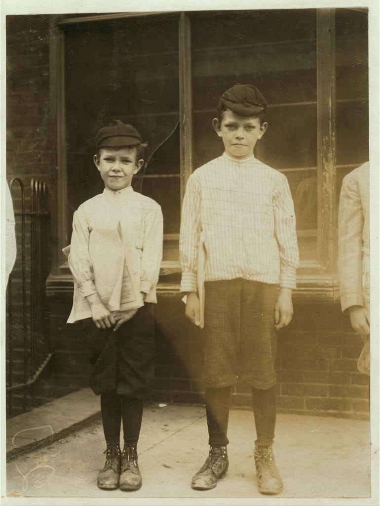 """William Lynch, 11 years of age, and Cornelius Lynch, 9 years of age, 607 [""""606"""" crossed out] E. 6th Street. Newsboys. William has been selling papers 4 years, average earnings 25 cents per week. Sells from choice. Don't smoke. Visits saloons. Works 5 hours a day. Cornelius selling 3 years, average earnings 35 cents a week. Earnings not needed at home. Sells from choice. Don't smoke. Visits saloons. Works 7 hours a day. Edward F. Brown, Investigator.  Location: Wilmington, Delaware / Photo by Lewis W. Hine."""