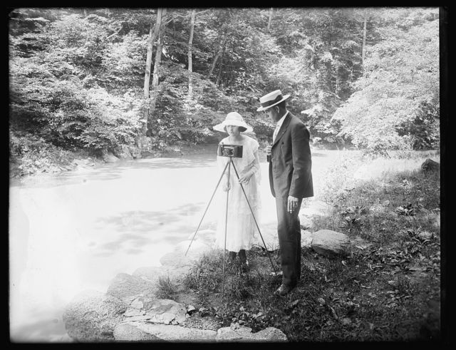 [Woman with camera and man in woodland setting]