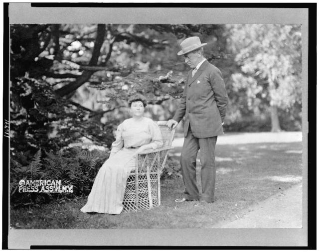 [Woodrow Wilson, full-length portrait, standing next to his wife, Ellen, seated in a chair]