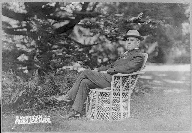 [Woodrow Wilson, full, seated in wicker chair on lawn of Prospect, his home at Princeton, N.J., facing left]
