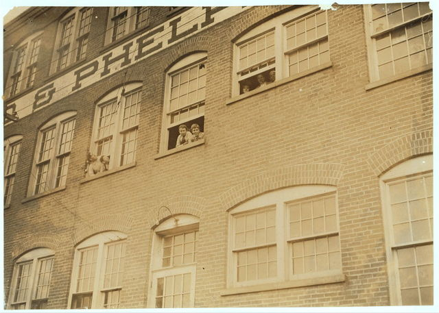 "Workers in Fargo & Phelps Shoe Co., Saw six boys and two girls probably under 14. Note face of very young girl in window. Large sign up, ""Boys Wanted.""  Location: Louisiana, Missouri."