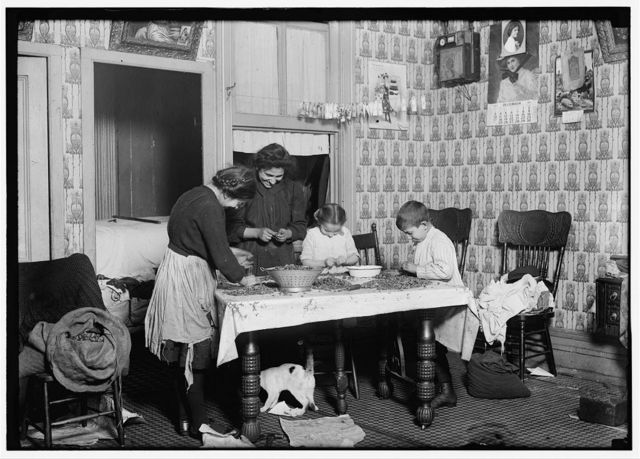 143 Hudson St., ground floor. Mrs. Salvia; Joe, 10 years old; Josephine, 14 years old; Camille, 7 years old. Picking nuts in a dirty tenement home. The bag of cracked nuts (on chair) had been standing open all day waiting for the children to get home from school. The mangy cat (under table) roamed about over everything. Baby is sleeping in the dark inner bedroom (3 yrs. old).  Location: New York, New York (State)