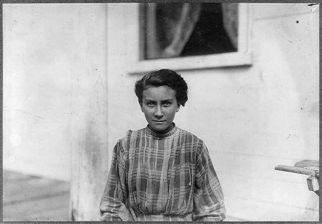 """A modest young French girl of 13 years. Spinner in the Spring Village Mill, runs six sides. Mr. Hine saw her working Sept. 2. Said, """"I'd rather work."""" Been working since last February.  Location: Winchendon, Massachusetts."""