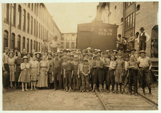"""A part of the spinning force working in the Washington Cotton Mills, Fries, Va. Group posed by the overseer. All work. The overseer said, """"These boys are a bad lot."""" All were alive to the need for being 14 years old when questioned.  Location: Fries, Virginia."""