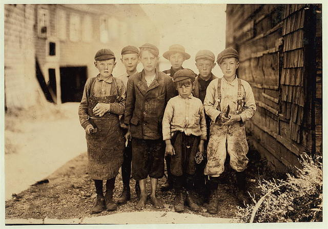 All these boys are cutters in the Seacoast Canning Co., Factory #7. Ages range from 7 to 12. They live near the factory. Seven year old boy in front, Byron Hamilton, has a badly cut finger, but helps his brother regularly. Behind him is his brother, George, 11 years. He cut his finger half off while working. They and many other youngsters said they were always cutting their fingers. (See photo #2435 and label.) George earns $1.00 some days, $.75 usually. Some of the others said they earn $1.00 when they work all day. At times they start at 7 A.M. Work all day, and until midnight, but the work is very irregular. Names of those in the photo are George Mathews, Johnny Rust, John Surles, Fulsom McCutchin (11 yrs.), Albert Robinson, Morris McConnell.  Location: Eastport, Maine.