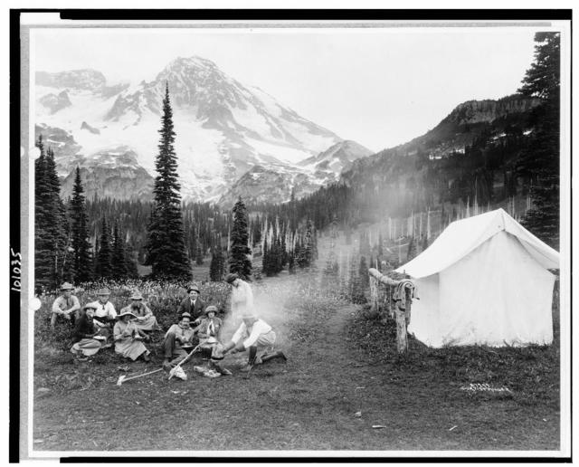 [Camping party of men and women cooking at campfire and eating near tent in Indian Henry, Mt. Rainier National Park, Washington] / Curtis & Miller.
