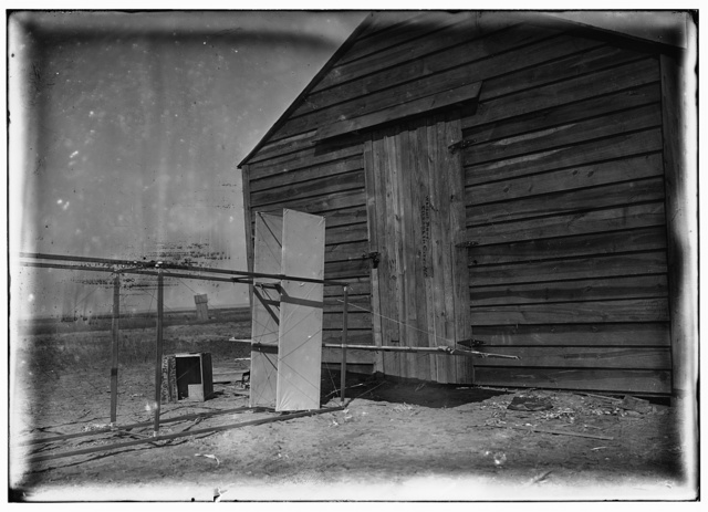 [Close-up view of rudders and elevator of glider in front of the camp building at Kitty Hawk, North Carolina]