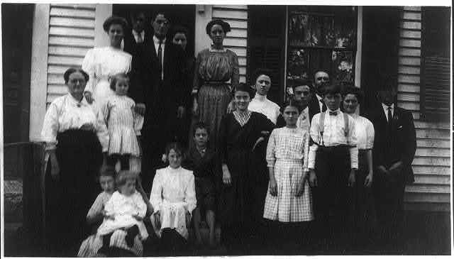 Family of Adrienne Pagnette: The three standing in front row are Adrienne, Anna and Francis. Adrienne, an adolescent French Illiterate. Speaks almost no English. Is probably 14 or 15. Doffs on top floor spinning room of Glenallen Mill. Anna, said she was 12 years old and helped older sister in Mill. Been at it all summer. She stands next Adrienne. Francis, has regular job doffing (see photo 239[...] [i.e., 2399?]). Says he is 15 but Mr. Hine Doubted it. Family consists of 17 members, 8 or 10 of them in the mill; almost every one of them illiterate. Stooping, reaching and pushing heavy boxes is bad for young girl adolescent.  Location: Winchendon, Massachusetts.