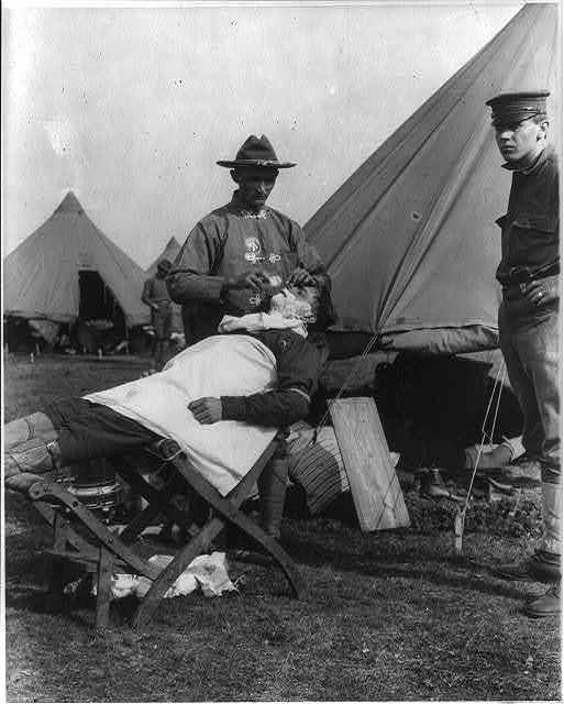 Fort Sam Houston, Tex., 1911-1912: field barber giving a shave