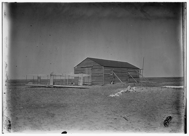 [Front view of glider outside camp building at Kitty Hawk, North Carolina ]