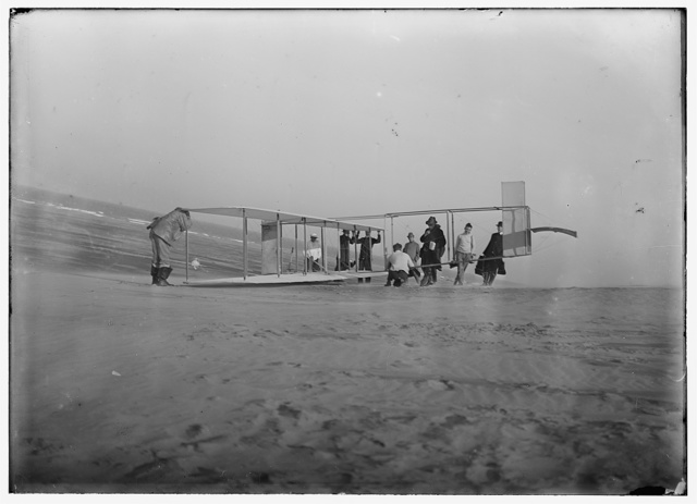 [Glider being prepared for flight by Orville and assistants; a number of reporters stand off to the right]
