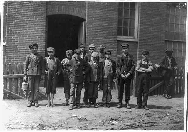 "[Group containing the following boys who work in the Sagamore Mfg. Company, Fall River. Manuel Corieiia [i.e., Correira] , 144 Cove St., works in Spinning room on top floor. Said, ""I only help mother."" He was apparently 13 or 14. Manuel Oliver, George Street, works in card room. Seems surely only 12 years old. Manuel Benevirdes, 30 Otto Street, works on top floor. Manuel Rage, 51 George Street, works in spinning room on fourth floor. John Oliver, 93 Slater Street, works in spinning room on third floor. Joseph Ariuda, 23 Shorr Street, works in spinning room on third floor.]  Location: Fall River, Massachusetts."