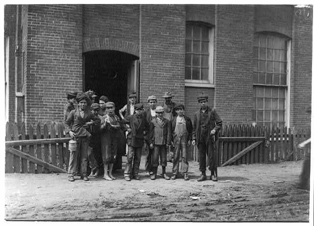"""Group containing the following boys who work in the Sagamore Mfg. Company, Fall River. Manuel Corieiia [i.e., Correira] , 144 Cove St., works in Spinning room on top floor. Said, """"I only help mother."""" He was apparently 13 or 14. Manuel Oliver, George Street, works in card room. Seems surely only 12 years old. Manuel Benevirdes, 30 Otto Street, works on top floor. Manuel Rage, 51 George Street, works in spinning room on fourth floor. John Oliver, 93 Slater Street, works in spinning room on third floor. Joseph Ariuda, 23 Shorr Street, works in spinning room on third floor.  Location: Fall River, Massachusetts."""