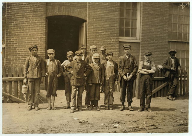 """[Group containing the following boys who work in the Sagamore Mfg. Company, Fall River. Manuel Corieiia [i.e., Correira] , 144 Cove St., works in Spinning room on top floor. Said, """"I only help mother."""" He was apparently 13 or 14. Manuel Oliver, George Street, works in card room. Seems surely only 12 years old. Manuel Benevirdes, 30 Otto Street, works on top floor. Manuel Rage, 51 George Street, works in spinning room on fourth floor. John Oliver, 93 Slater Street, works in spinning room on third floor. Joseph Ariuda, 23 Shorr Street, works in spinning room on third floor.]  Location: Fall River, Massachusetts."""