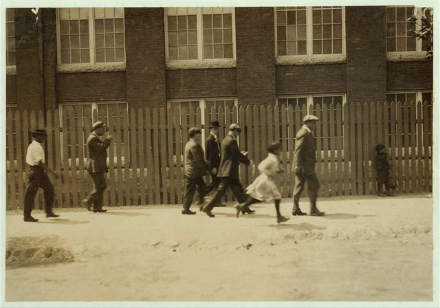 Group going out at noon from the Kilburn Mills. Little girl running is one of the workers.  Location: New Bedford, Massachusetts.