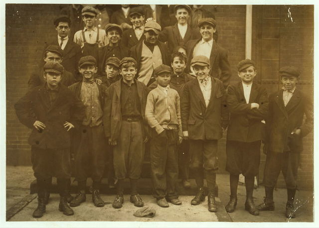 "Group in front of Office Steps. Boy on left end (in front) ran away when I tried to get his name. A companion said, ""He ain't got no time to sell postals. He got to go to night school."" Another said, ""His name is Jo Traain and [he] lives on West St."" Three others of the smallest in front are: Andrew Stefanik, 4 Exchange St. (very young), a ""spare boy"" has worked 9 months there. At 1 P.M., Mr. Hine saw his going away from the mill and followed him up town. He said, ""Boss laid me off for a day. He does that sometimes. Then I bum around town."" Joseph Mile, 80 Tremont St., In spinning room 1 and 2. Joseph Maslak, 34 Front St. of 3 Depto St. Works in Cloth Room. Last night he gave me his name as John Mak. To-day he corrected it.  Location: Chicopee, Massachusetts."