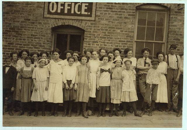 Group of workers in Danville, (Va.) Knitting Works, Only a few of them would pose. I watched them going to and coming from work; also went through the factory during working hours. One morning I counted eighteen that I judged to be under fourteen, several of them were under twelve, and one about nine years. I saw them working and helping. The youngest ones dodged the camera.  Location: Danville, Virginia.