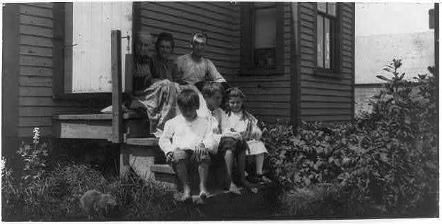 Hamilton Family, sardine works, Eastport. Father earns $15 to $25 a week irregularly during the work season for three months. Said that 20 years ago he made $5 a day as a boy, cutting. The mother is a packer makes $10 a week and upward, during the active season. Another boy, not in the photo, works also. In the front row are George Hamilton, 11 years old, who cuts regularly--made a dollar in three hours the day before; Byron, with a badly cut finger, earns 25 cents a day; little Erna 8 years old works at cartoning. The father is dissatisfied with the irregular income, but cannot see the connection between his early boyhood work and his present stagnation. He is putting his little ones through the same process.  Location: Eastport, Maine.