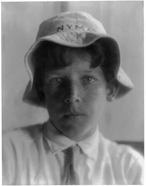 [K. Sanborn in N.Y.M.A. beach hat and shirt and tie]
