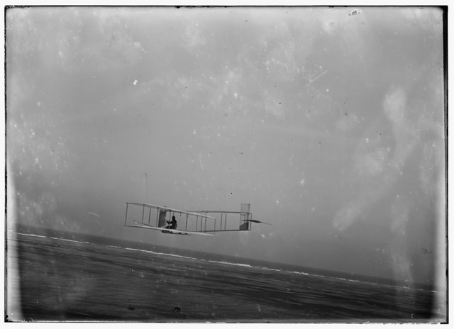 [Left rear view of glider at a low altitude, showing the fixed vertical fin attached to a front strut; Kitty Hawk, North Carolina]