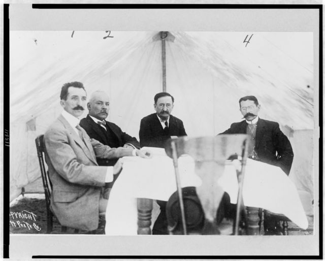 [Mexican Peace Commissioners José María Pino Suárez, Dr. Vazquez Gomez, Francisco I. Madero, and Judge Carbajal seated around table, during the Mexican Peace Commission at Ciudad Juarez, during the revolution against the Diaz government]