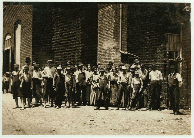 "Noon-hour at Riverside Cotton Mills, Danville, Va. All are workers. The Supt., who posed them, said, ""Be sure not to get any little dinner-toters in the photo. We have none working under fourteen."" I did see some but not many.  Location: Danville, Virginia."