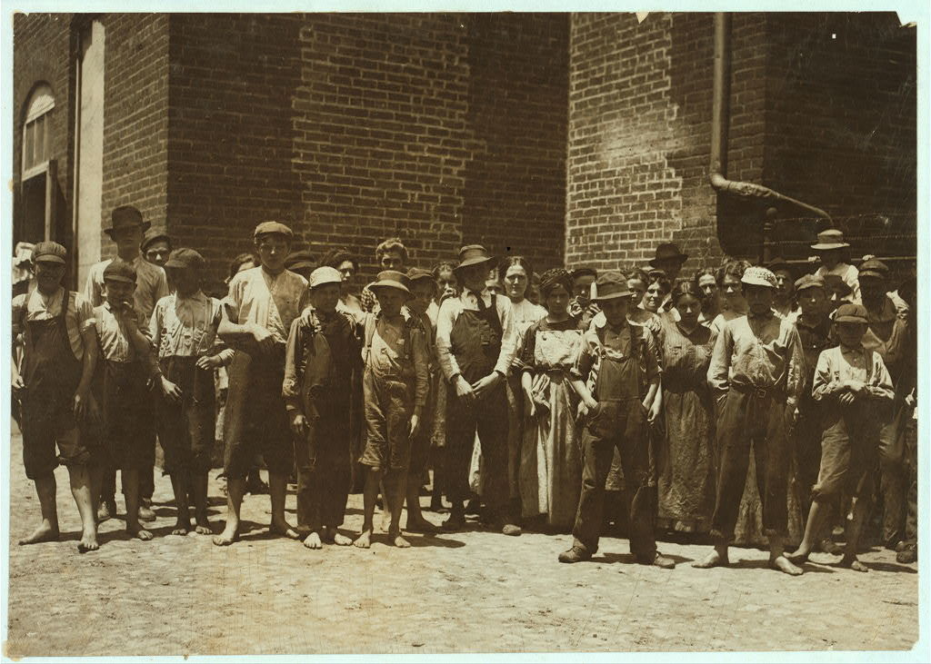 "Noon-hour at Riverside Cotton Mills, Danville, Va. All are workers. The Supt. who posed them, said, ""Be sure not to get any little dinner-toters in the photo. We have none working under fourteen."" I did see some but not many.  Location: Danville, Virginia."