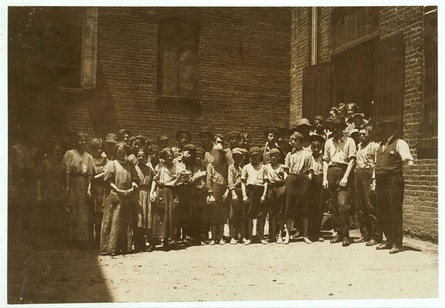 """Noon-hour at Riverside Cotton Mills, Danville, Va. All are workers. The Supt., who posed them, said, """"Be sure not to get any little dinner-toters in the photo. We have none working under fourteen."""" I did see some, but not many.  Location: Danville, Virginia."""