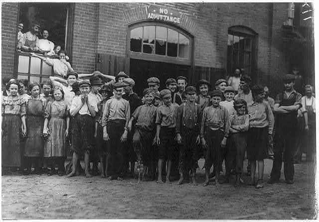 Noon-hour at the Riverside Cotton Mills, Danville, Va. Group of spinners, doffers, etc. All work. Some here are surely under fourteen, but not many.  Location: Danville, Virginia.