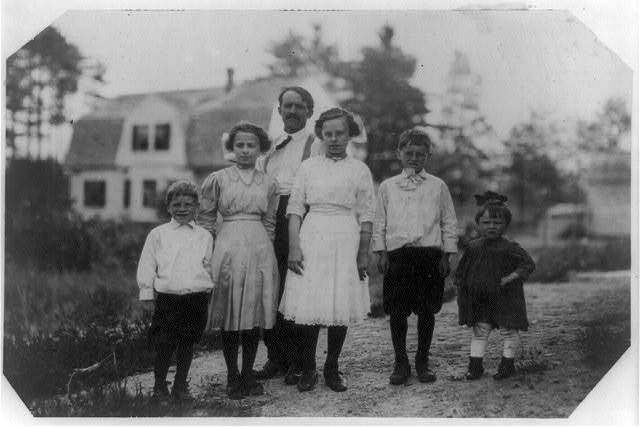 Part of the family of Eva Tanguay, 61 Sylvester St., doffer in spinning room of Ayer mill. A half hour car ride in a crowded, stuffy car to and from work. Leaves home at 6 A.M. and returns at 6:30 P.M. The doffing work is standing and riding--bad for an adolescent girl. Father is a carpenter. Oldest brother is 11 years old, her sister  Muriel in middle of front row said she was 11 years old but I doubt it. Eva is on left end of front row. Said she was 14 but doubtful.  Location: Lawrence, Massachusetts.