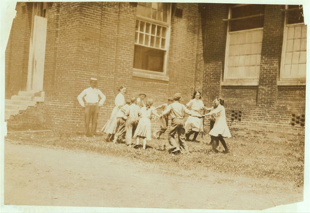 """""""Ring around the rosy."""" Supt. and overseers with the """"Relief Crowd,"""" in Yazoo City (Miss.) Yarn Mills. The Supt. said, """"We relieve all children under sixteen for two hours a day except the doffers. They go out and play."""" Then turning to the children he said, """"Now play."""" They eyed him blankly, """"Play wot?"""" """"Oh, play anything."""" Before they could do it, however, he had to pose them himself (see photo 2106) which was especially posed for the occasion. In this photo, note the disparity between the (alleged) ages of the younger ones who said that they were 12 and thirteen, and the older ones, who said fifteen years old.  Location: Yazoo City, Mississippi."""