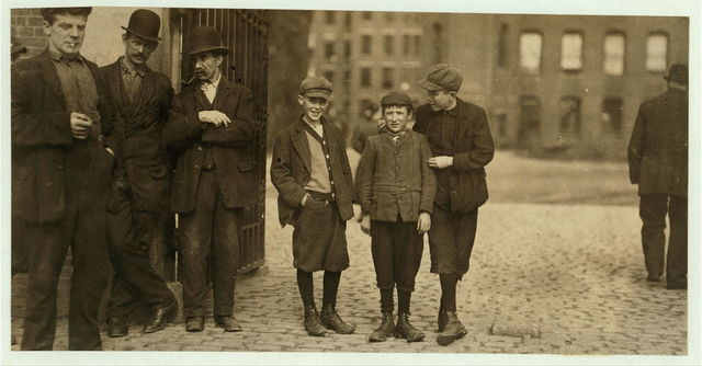 Robert Magee (smallest), 270 Suffolk St., apparently 12 years, been working in Mule Room #1 Merrimac Mill, Lowell, one year. Michael Keefe (next in size) 32 Marion St., been at work in #1 Mule Room, Merrimac Mill, Lowell, for eight months; apparently 13 years old. Cornelius Hurley, 298 Adams St., been at work in #1 Mule Room, Merrimac Mill, Lowell, for six months; about 13 or 14 probably.  Location: Salem, Massachusetts.