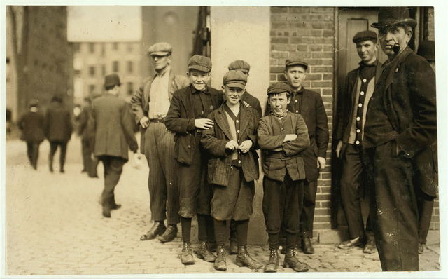 Robert Magee (smallest). 270 Suffolk St., Apparently 12 years old Been working in Mule Room #1, Merrimac Mill, Lowell, 1 year. Michael Keefe (next in size), 32 Marion St., been working in #1 Mule Room, Merrimac Mill, Lowell, for 8 months, about 13 or 14. Cornelius Hurley, 298 Adams St., been at work in #1 Mule Room, Merimac Mill, Lowell, for 6 months, about 13 or 14.  Location: South Framingham, Massachusetts.